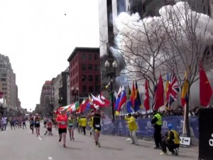 Runners prepare to cross the finish line as the first explosion occurs