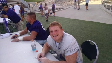 K-State's Ryan Mueller (right) and B.J. Finney sign autographs during Saturday's Fan Appreciation Day.