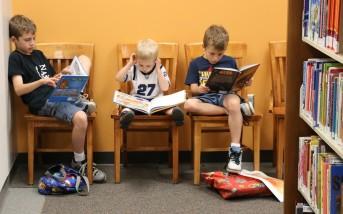 Michael, Benjamin, and Nathan Dunaway reading at the library.