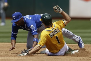 Kansas City Royals Alcides Escobar, left, tags out Oakland Athletics' Billy Burns (1) in the third inning of a baseball game Sunday, June 28, 2015, in Oakland, Calif. Burns was forced out on a single by Oakland's Eric Sogard. (AP Photo/Ben Margot)