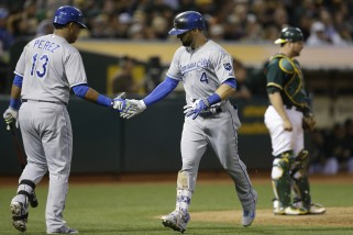 Kansas City Royals' Alex Gordon, right, is congratulated by Salvador Perez (13) after Gordon hit a home run off Oakland Athletics' Jesse Hahn in the sixth inning of a baseball game Friday, June 26, 2015, in Oakland, Calif. (AP Photo/Ben Margot)