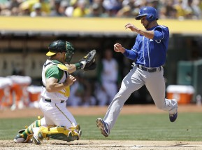 Kansas City Royals' Omar Infante, right, scores past Oakland Athletics catcher Stephen Vogt in the third inning of a baseball game Saturday, June 27, 2015, in Oakland, Calif. Infante scored on a sacrifice fly hit by Royals' Mike Moustakas.  (AP Photo/Ben Margot)