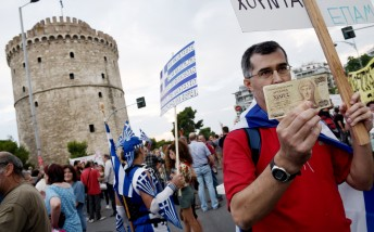? supporter of the NO vote in the upcoming referendum, holds an old 1,000 drachma bank note during a rally in the northern Greek port city of Thessaloniki, Monday, June 29, 2015. Anxious Greek pensioners swarmed closed bank branches and long lines snaked at ATMs as Greeks endured the first day of serious controls on their daily economic lives ahead of a July 5 referendum that could determine whether the country has to ditch the euro currency and return to the drachma. (AP Photo/Giannis Papanikos)