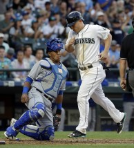 Seattle Mariners' Kyle Seager crosses home while scoring on a bases-loaded walk as Kansas City Royals catcher Salvador Perez watches during the fourth inning of a baseball game Tuesday, June 23, 2015, in Seattle. (AP Photo/Elaine Thompson)