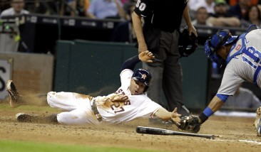 Houston Astros' Jose Altuve (27) slides past the tag from Kansas City Royals catcher Salvador Perez to score from third base on a Chris Carter fielder's choice in the seventh inning of a baseball game Wednesday, July 1, 2015, in Houston. (AP Photo/Pat Sullivan)