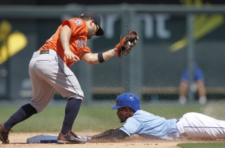 Kansas City Royals' Jarrod Dyson, right, steals second base as Houston Astros second baseman Jose Altuve, left, get the late throw from catcher Jason Castro in the eighth inning of a baseball game at Kauffman Stadium in Kansas City, Mo., Sunday, July 26, 2015. The Royals beat the Astros 5-1. (AP Photo/Colin E. Braley)