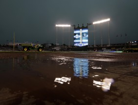 Rainwater pools on the field at Kauffman Stadium before a baseball game between the Kansas City Royals and the Tampa Bay Rays Monday, July 6, 2015, in Kansas City, Mo. The game was postponed and will be replayed Tuesday as the first game of a doubleheader. (AP Photo/Charlie Riedel)
