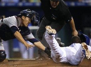Minnesota Twins catcher Kurt Suzuki, left, misses the tag on Kansas City Royals' Lorenzo Cain, right, during the 10th inning of a baseball game at Kauffman Stadium in Kansas City, Mo., Friday, July 3, 2015. The Royals defeated the Twins 3-2 in 10 innings. (AP Photo/Orlin Wagner)
