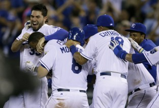 Kansas City Royals' Eric Hosmer, left, mobs teammate Alcides Escobar with Mike Moustakas (8) and Cheslor Cuthbert (19) following his game-winning hit during the tenth inning of a baseball game against the Houston Astros at Kauffman Stadium in Kansas City, Mo., Saturday, July 25, 2015. The Royals defeated the Astros 2-1 in ten innings. (AP Photo/Orlin Wagner)