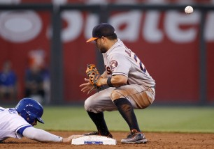 Houston Astros second baseman Jose Altuve, right, is unable to hold onto a throw from pitcher Scott Kazmir as Kansas City Royals' Mike Moustakas, left, dives back to second base on a pickoff attempt in the fourth inning of a baseball game in Kansas City, Mo., Friday, July 24, 2015. (AP Photo/Colin E. Braley)
