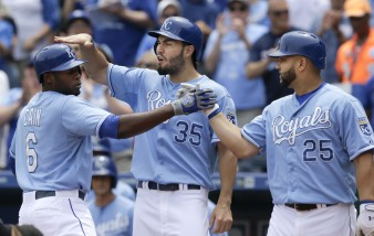 Kansas City Royals' Lorenzo Cain (6) is congratulated by teammates Eric Hosmer (35) and Kendrys Morales (25) after his two-run home run off Tampa Bay Rays starting pitcher Nathan Karns during the first inning of a baseball game at Kauffman Stadium in Kansas City, Mo., Thursday, July 9, 2015. (AP Photo/Orlin Wagner)