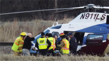Emergency crews transport a crash victim to a Life Star helicopter. Riley County EMS Director Larry Couchman said at the scene the victim was in critical condition and was being transported to Topeka.