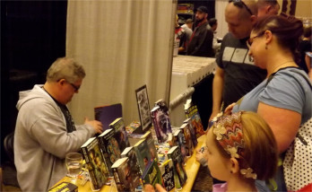 Novelist and senior writer at Hallmark Cards in Kansas City, Mo., Kevin Dilmore, readies a book for a family at the Little Apple Comic Con Saturday.