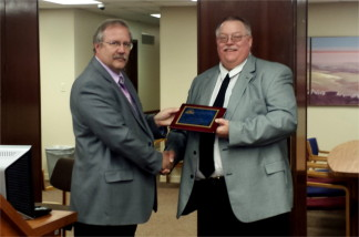 Riley County Emergency Management Director Pat Collins, right, receives the 2015 KEMA Professional of the Year Award from Geary County Emergency Management Director Garry Berges during Monday morning's Riley County Commission meeting. (Staff photo by Brady Bauman)